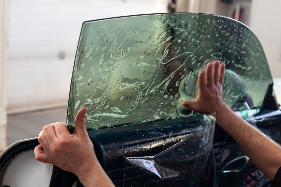 The wizard for installing additional equipment sticks a tint film on the side front glass of the car and flattens it by hand to fit the glass with a greenish tint in the auto service.